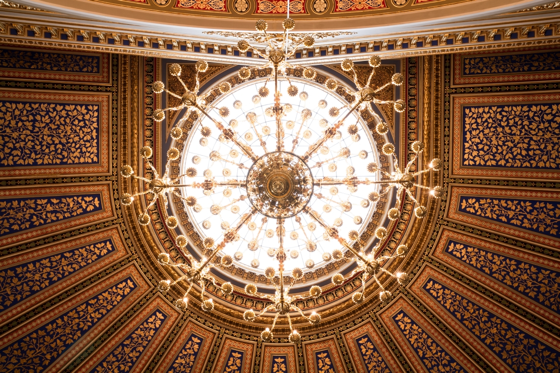 View from right below, up at a ceiling with a chandelier. Photo.